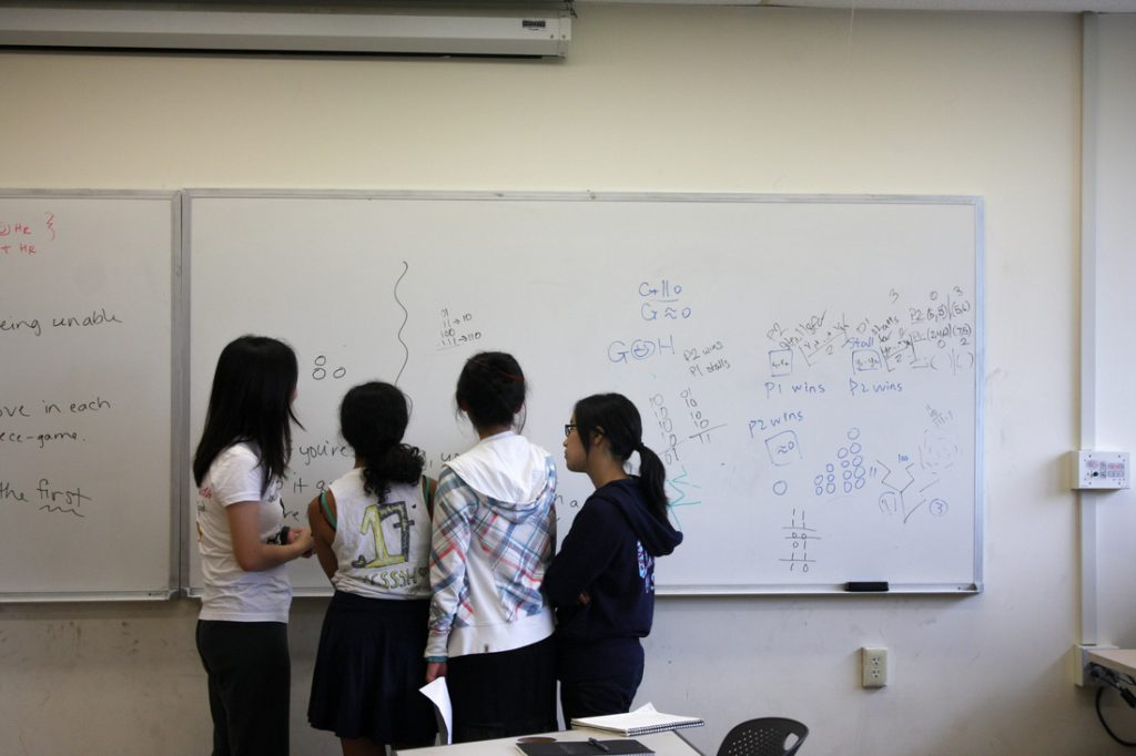 Four HCSSiM students working at a whiteboard